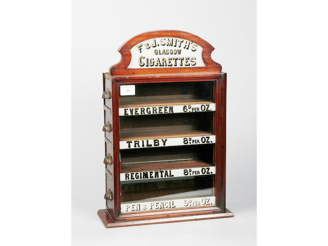An early 20th century mahogany and glass advertising display stand for cigarettes