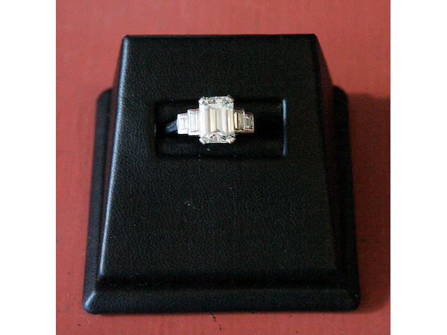 A rectangular-cut diamond ring with diamond shoulders