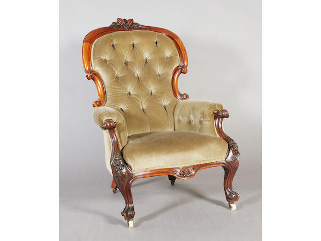 A mid-Victorian carved mahogany frame upholstered gentleman's armchair