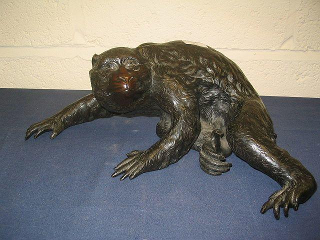 A Japanese bronzed metal model of a crouching ape Meiji period