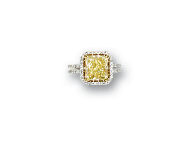 A fancy yellow diamond and diamond ring