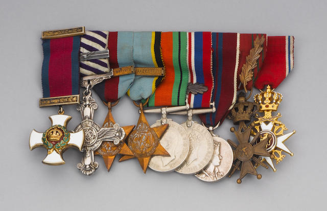 An assortment of military decorations, log books, certificates, photos, and warrants.