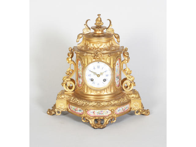 A late 19th century French gilt brass foliate cast and porcelain mounted mantel clock