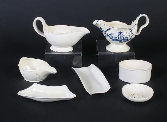 A creamware blue and white sauceboat, two others, an egg drainer and three other pieces Late 18th Century
