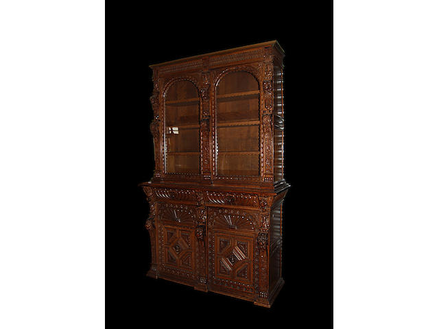 A Victorian carved oak glazed bookcase on cupboard