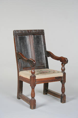 A mid 17th century oak panel back armchair