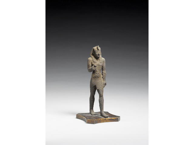 An Egyptian bronze striding figure of a pharaoh