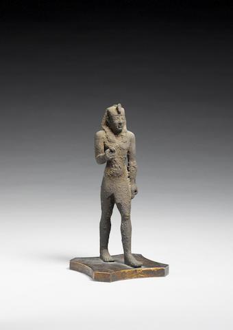 An Egyptian bronze striding figure of a pharaoh
