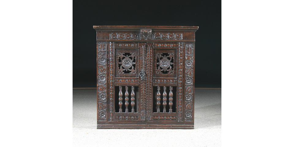 A late 17th Century oak mural glass/livery cupboard