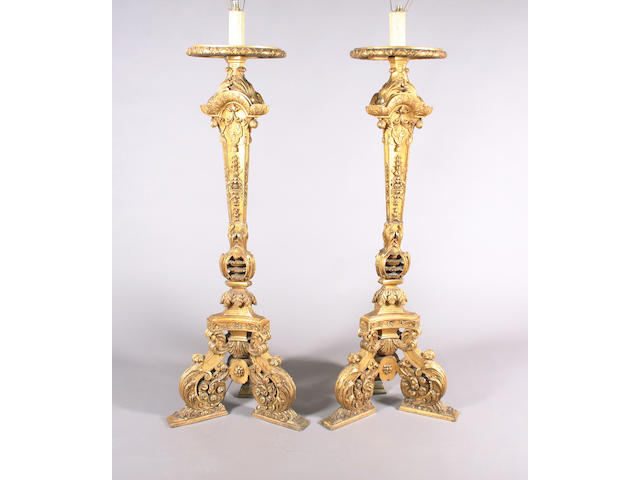 An elaborate pair of late 19th century Baroque design carved giltwood torcheres