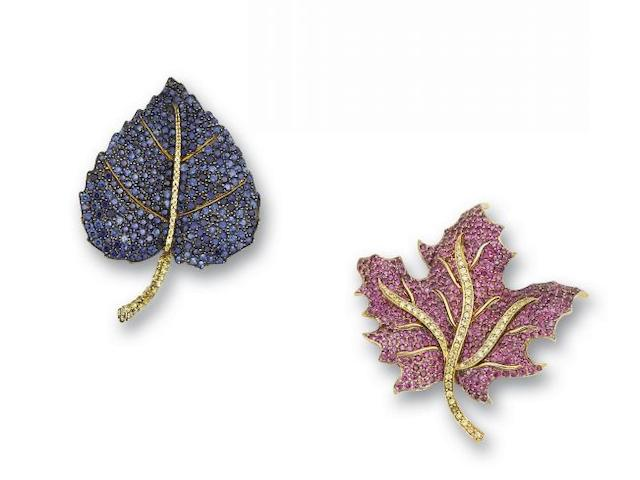 A set of two gem set leaf brooches