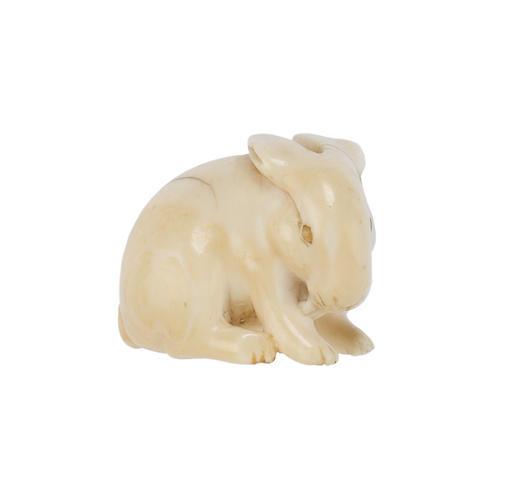 An ivory netsuke of a seated rabbit; signed Ranichi