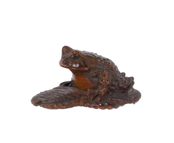 A wood netsuke, carved as a toad on a sandal by Masanao