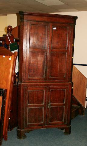 An early 19th Century oak floor standing corner cupboard