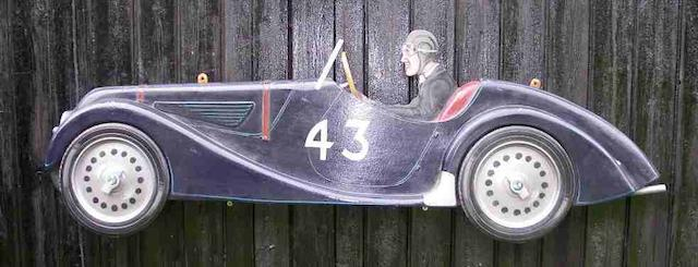 A hand painted wooden profile of a BMW 328,