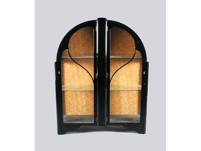 An Art Deco black finish china cabinet of arched form