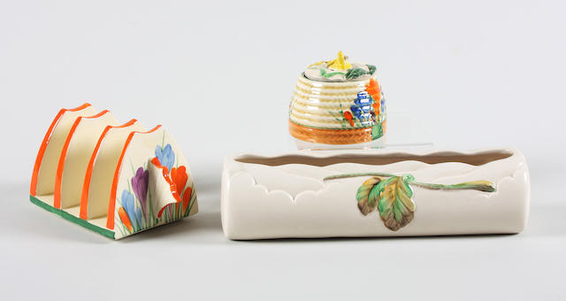A Clarice Cliff Bizarre 'Crocus' toast rack, a Clarice Cliff Bizarre 'Crocus' honey pot with associated cover and a Clarice Cliff moulded pentray