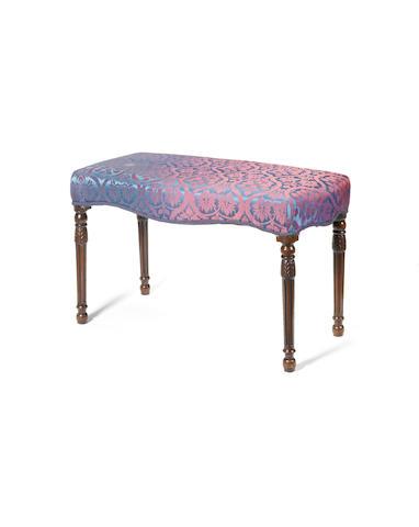 A George III carved mahogany serpentine stool circa 1790