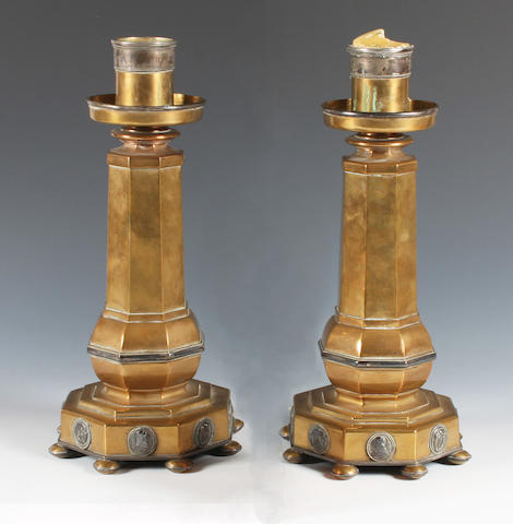 A pair of Arts and Crafts brass and electroplate mounted candlesticks in the style of Henry Wilson