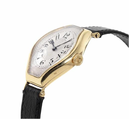 Patek Philippe. A fine and rare 18ct gold tonneau shaped and curved wristwatch Case No.287233, Movement No.192948, circa 1920