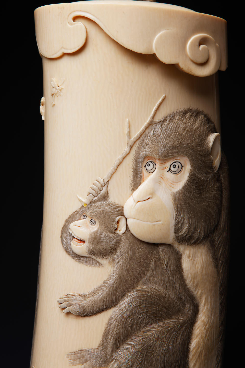 A large ivory tusk tusk carved with a monkey, on wood stand