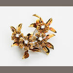 A diamond and gold brooch of floral design