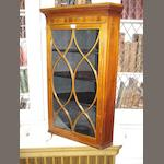 An Edwardian mahogany and chequer banded corner cupboard