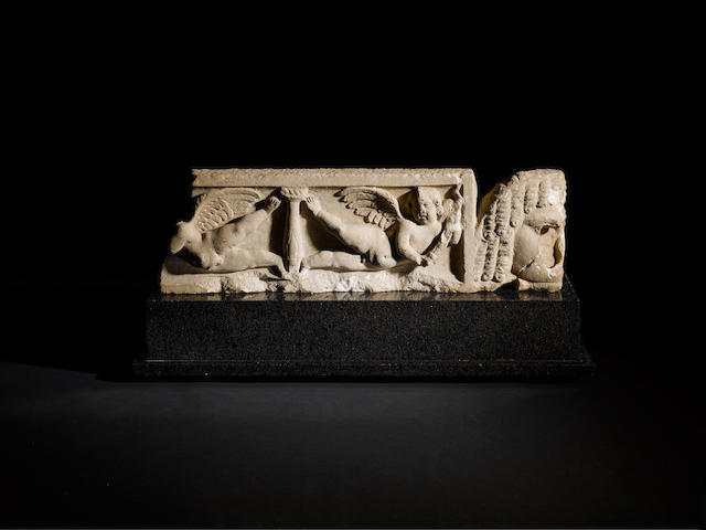 A Roman marble sarcophagus lid with two erotes and a comic mask