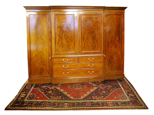 A large figured mahogany and inlaid breakfront clothes press, early 19th Century