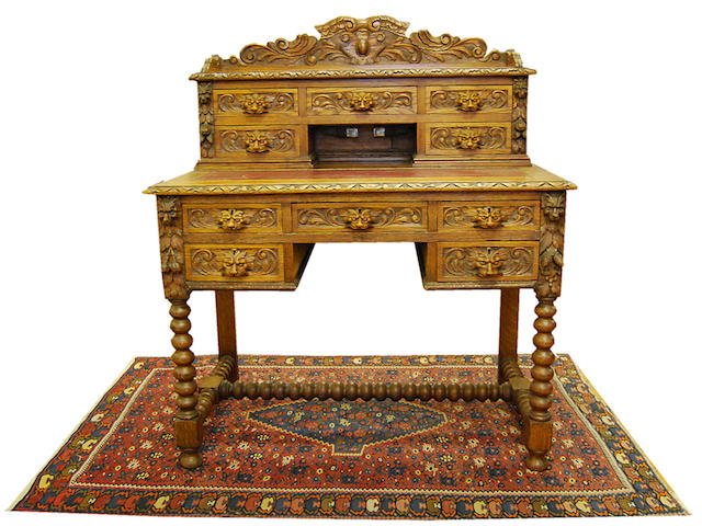 A late Victorian carved oak writing table
