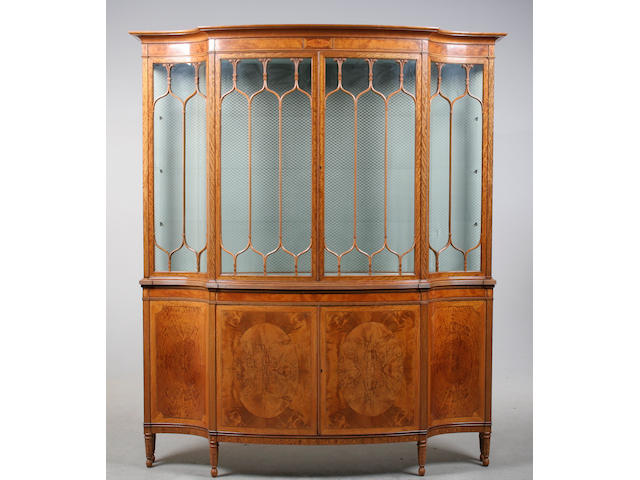 A good early 20th century flame satinwood serpentine display cabinet by Maples circa 1915