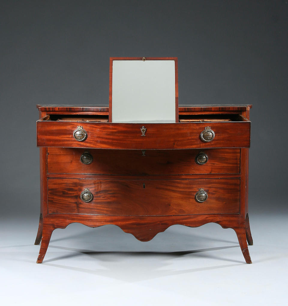 A George III mahogany serpentine Dressing Chest in the manner of John Cobb