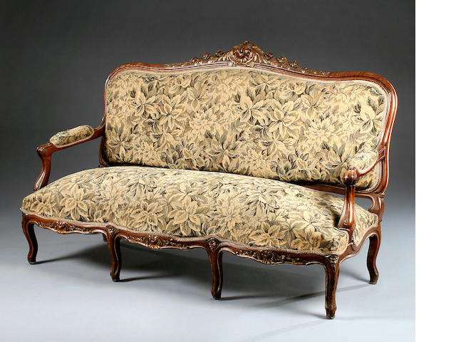 A large carved walnut sofa, in the Louis XV taste, circa 1900,