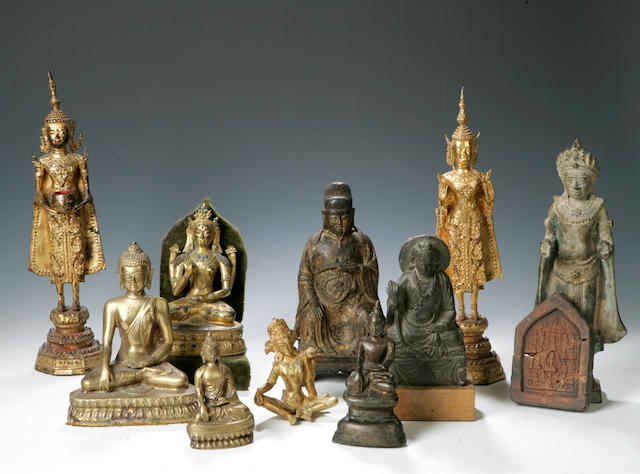 A collection of metal figures of Buddha and others