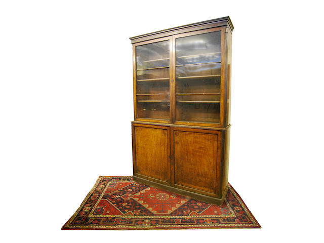 A large George IV mahogany and ebony-strung bookcase on cupboard