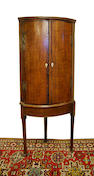 A George III oak and mahogany bow-front corner cupboard on stand