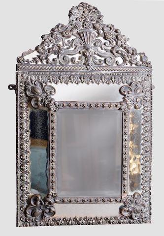 A Dutch embossed brass framed mirror