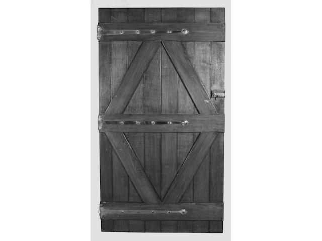 A scarce group of nineteen Arts and Crafts style planked oak doors, in the manner of C.F.A. Voysey