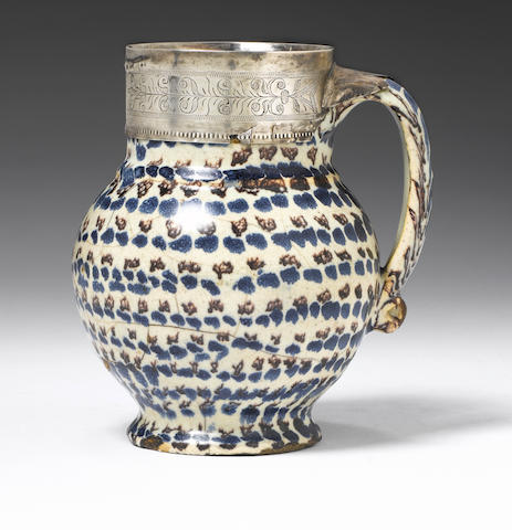 An English delft mug with English silver mount dated 1620