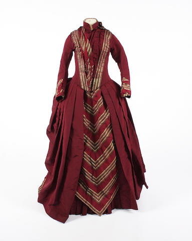 A aubergine silk late 19th century dress with green striped contrast
