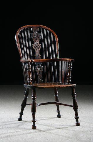 A yew-wood high back Windsor arm chair, mid-19th Century