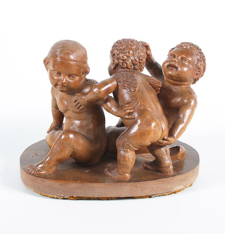 An 18th century carved fruitwood group of three intertwined cherubs