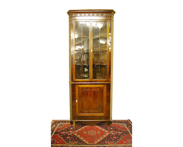 A mahogany and glazed standing double corner cupboard, early 19th Century