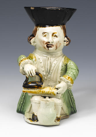 (-)  A fine 'Tailor' Toby Jug from the Midshipman Family, c. 1780, seated holding an iron on an iron
