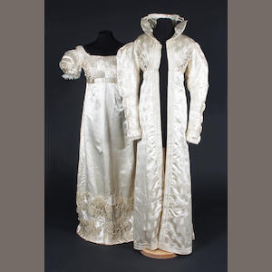 A early 19th century redingote of figured cream silk and a cream silk dress
