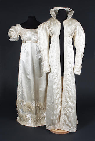 An early 19th century redingote of figured cream silk and a cream silk dress