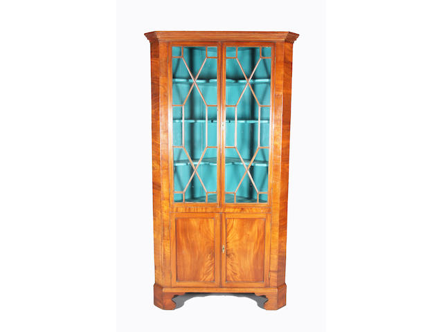 A George III figured mahogany one-piece floorstanding corner cupboard