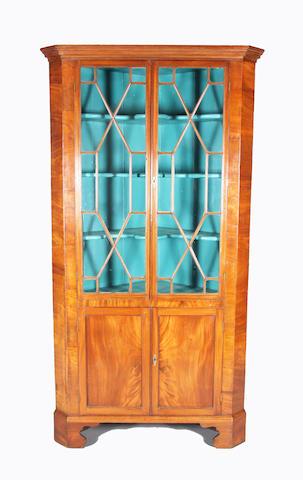 A George III figured mahogany one-piece floorstanding corner cupboard