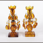 A pair of amber coloured glass candlestick lustres