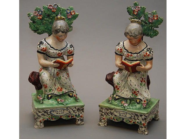A pair of Staffordshire Village maid table base figures Circa 1830, each modelled as a lady reading a book, seated before brocage (2)